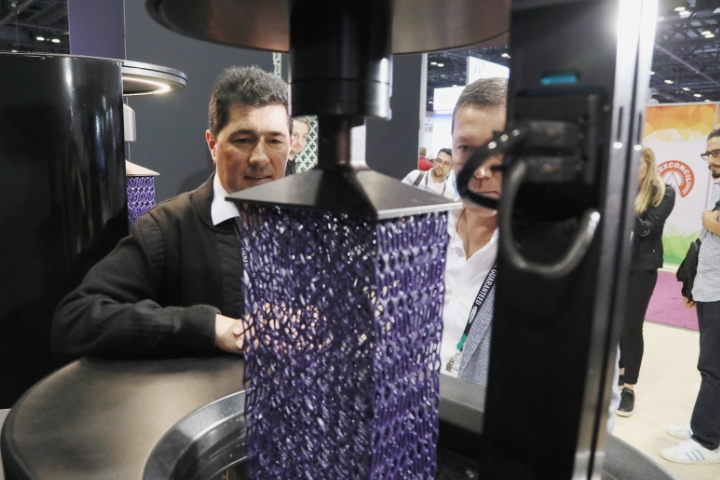 Two men examining a 4D printed item in the 3D and 4D printing zone.
