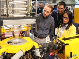Three attendees inspecting a machine at NPE.