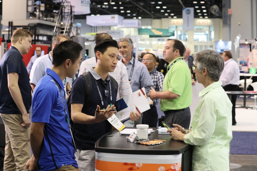 A group of attendees discussing on the show floor.