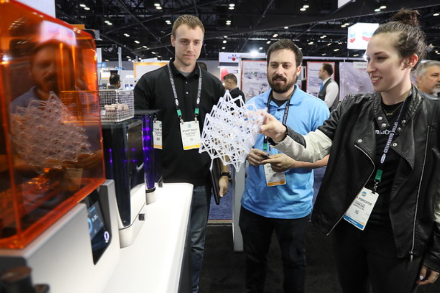 A group of attendees examining a 4D printed object in a Technology Zone.